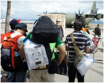 Figure 1 Aid workers in Tacloban City, Philippines after Typhoon Haiyan bring SolarBags for their own use.